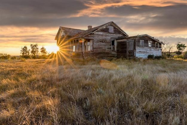 カナダの大草原の日没時に農場の放棄された家