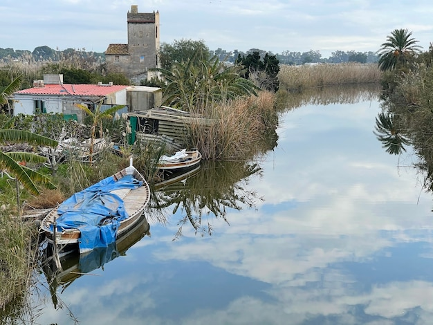 Abandoned house and boats in the wetland of el palmar. valencian countryside, spain