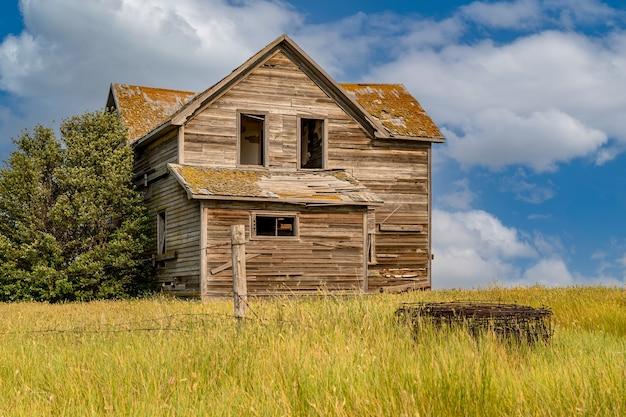 カナダのサスカチュワン州の農場にある廃屋で、前景に有刺鉄線があります