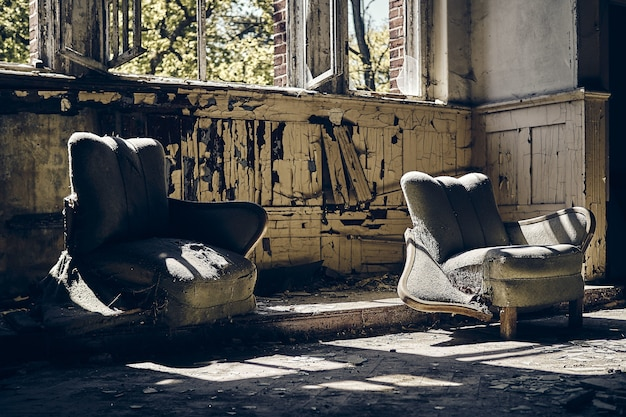 Abandoned house with two worn-out sofas and broken windows during daytime
