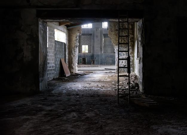 放棄された工業用インテリア。床に瓦礫、割れたガラス、木製の階段がある古い工場