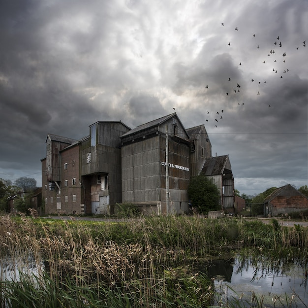 Abandoned mill with a dark sky and birds flying in north norfolk, uk