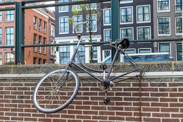 네덜란드 암스테르담 운하 벽에 바퀴 하나가 매달려 있는 버려진 오래된 자전거