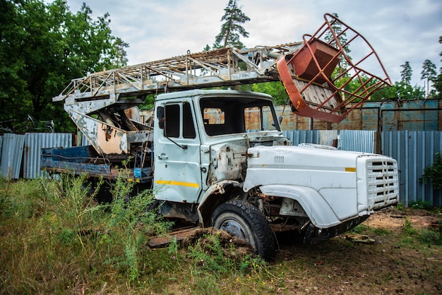 Abandoned old truck in a clearing, grunge equipment, disassembled broken