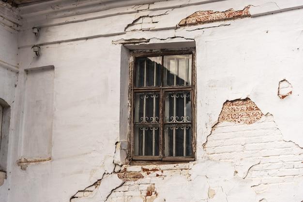 더러운 벽돌 벽과 창문 유리가 손상된 버려진 또는 방치 된 집. 시골이나 가난한 나라의 풍화 주거. 마을이나 도시에 버려진 오래된 건물의 지저분한 외관