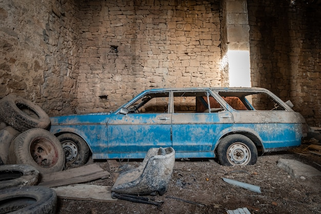 Abandoned and rusty blue car