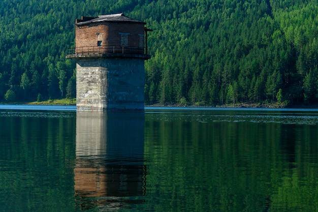 호수가 된 범람된 채석장 한가운데 있는 펌핑 스테이션의 버려진 타워