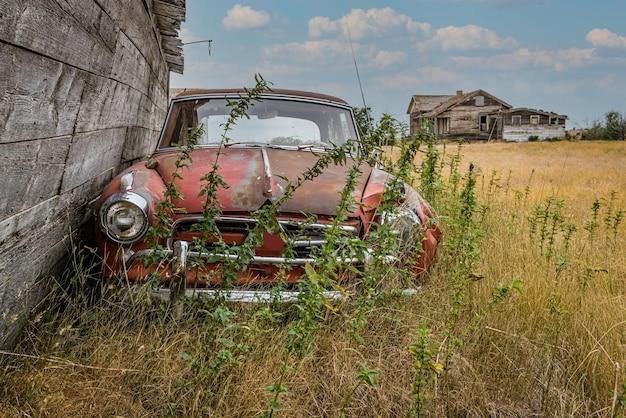 Заброшенный старинный автомобиль во дворе заброшенного дома в прериях саскачевана в канаде