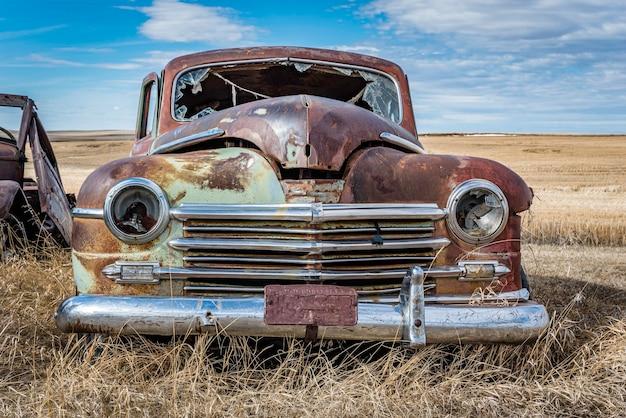 Заброшенный старинный зеленый автомобиль в прериях в саскачеване