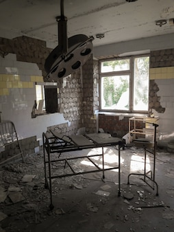Abandoned ward in a destroyed hospital with rusty equipment and a broken window