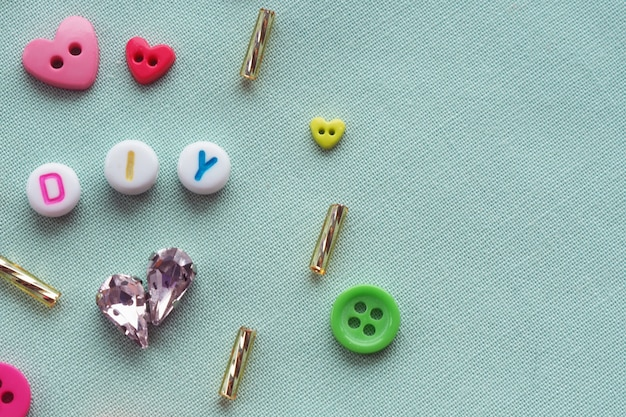 Abbreviation of diy plastic beads among buttons, crystals, glass beads on a blue fabric background.do it yourself concept
