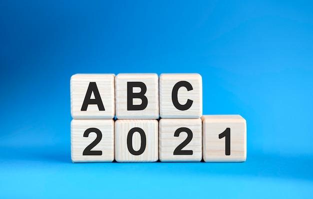 青い背景の上の木製の立方体のabc 2021年