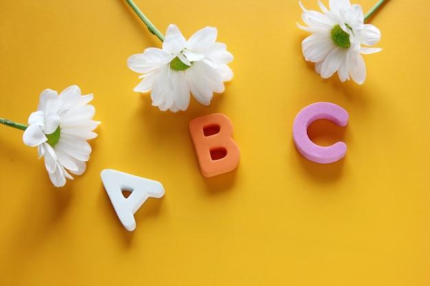 Abc  - 英語のアルファベットの最初の文字と3つの白い菊