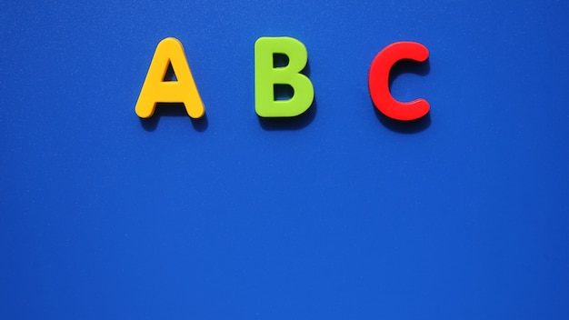 Abc first letters of the english alphabet on a blue background. english for beginners. copy space.