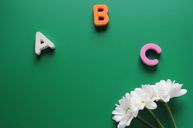 Abc - the first letters of the english alphabet and three white chrysanthemums