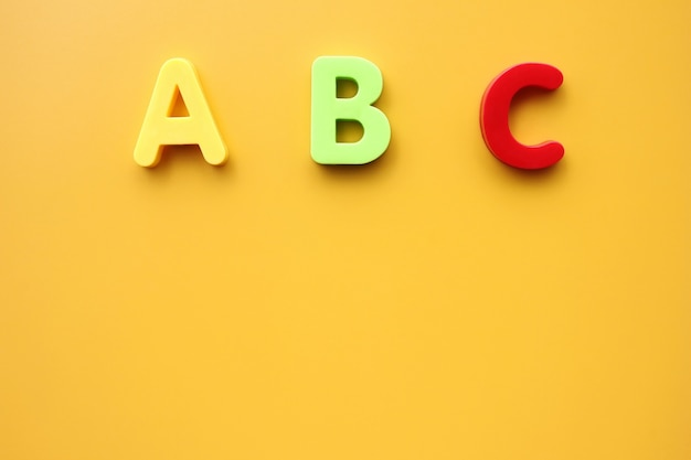 Abc first letters of the english alphabet on a yellow background.  copy space.
