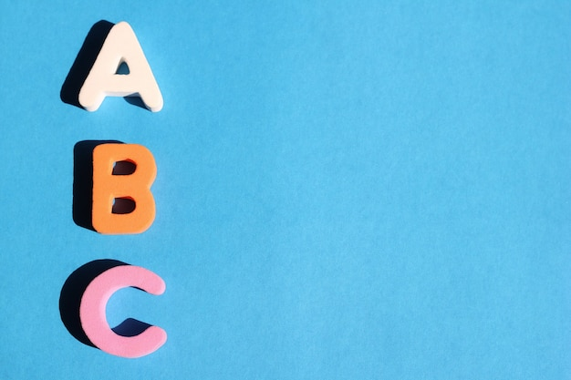 青の背景に英語のアルファベットのabcの最初の文字。スペースをコピーします。