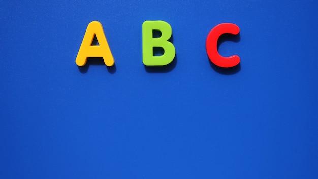 青の背景に英語のアルファベットのabcの最初の文字。初心者のための英語。スペースをコピーします。