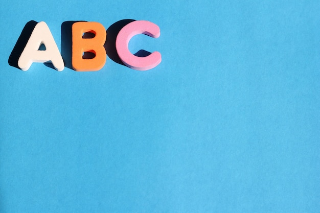 青の背景に英語のアルファベットのabcの最初の文字。初心者のための英語。
