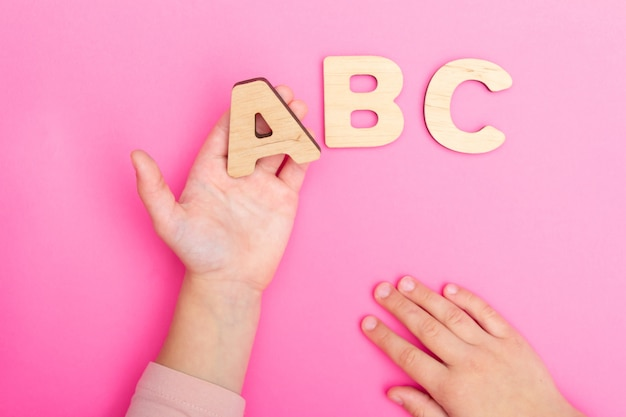 Abc letters in child's hands on pink background