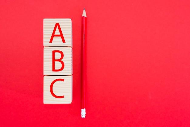 赤い背景に赤い鉛筆で柱の形で木製の立方体のブロック上のアルファベットのabc文字。スペースをコピーします。