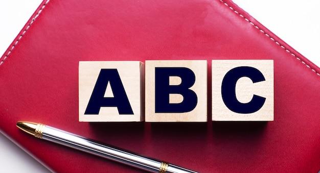 Abcは、ペンの近くのバーガンディのノートに立つ木製の立方体で構成されています