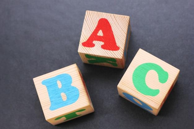 Abc-木のおもちゃのブロックの英語のアルファベットの最初の文字。外国語を学ぶ。初心者のための英語。