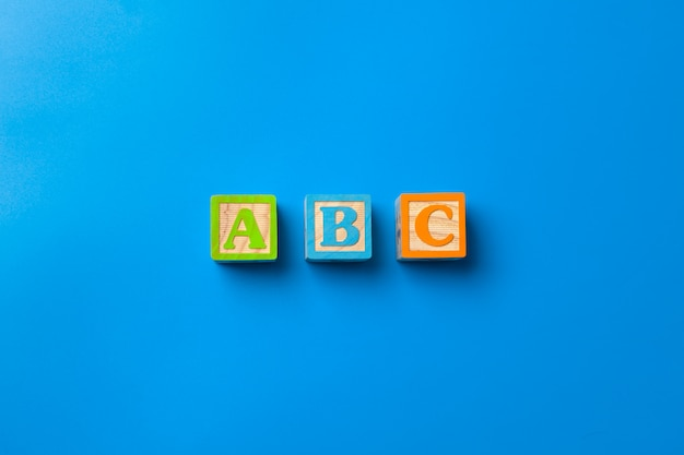 Abc. wooden colorful alphabet blocks on blue background, flat lay, top view.