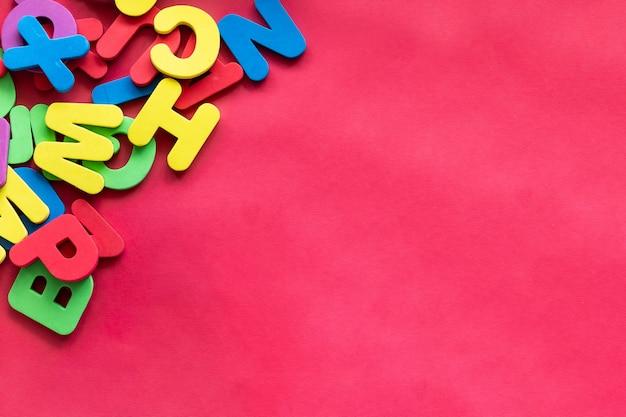 Буквы алфавита в разные цвета на красном фоне. алфавит, abc, концепция образования