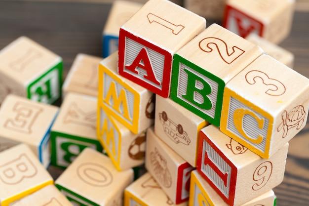Алфавит преграждает abc на деревянном столе.