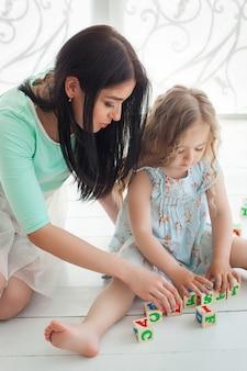Маленькая милая девушка и ее мать играя и давая образование с кубами abc внутри помещения. молодая милая мать и ее дочь играя блоки.