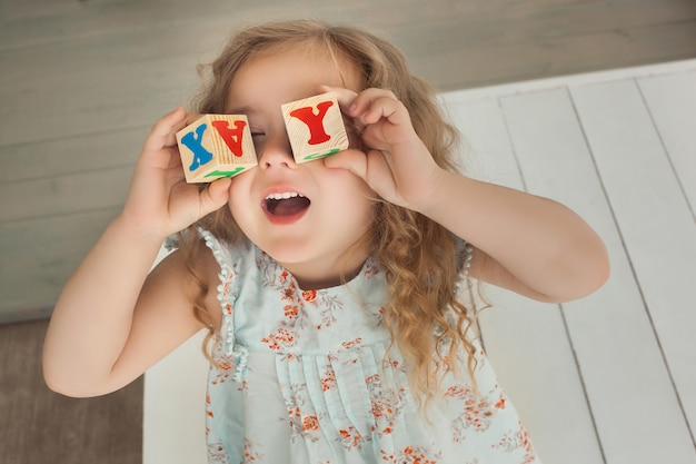 Довольно маленькая милая девушка с удовольствием в помещении. милый ребенок играя с кубами abc. милая девушка крупным планом портрет.
