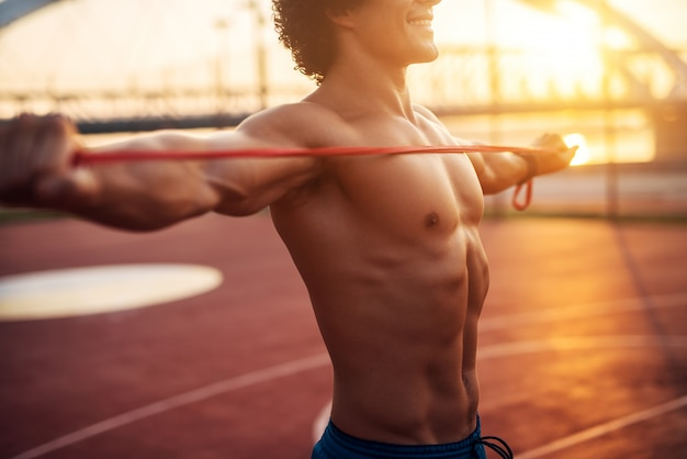 Abdominal muscles of young strong shirtless man training outside