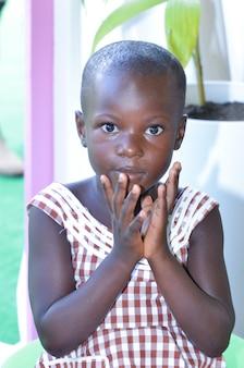 아비장 - 아이보리 코스트 - 2015년 12월 1일: 카메라를 직접 바라보는 8세 아이보리앙 여학생, 웃고 있는 귀여운 아프리카 아이의 초상화