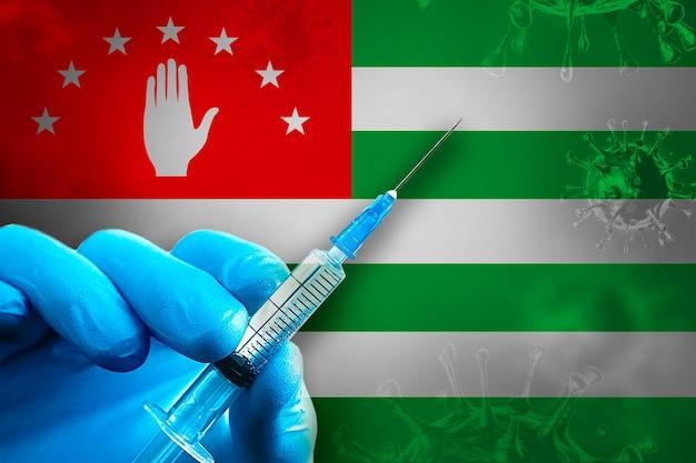 Abkhazia covid19 예방 접종 캠페인 파란색 고무 장갑을 끼고 깃발 앞에 주사기를 들고 있습니다
