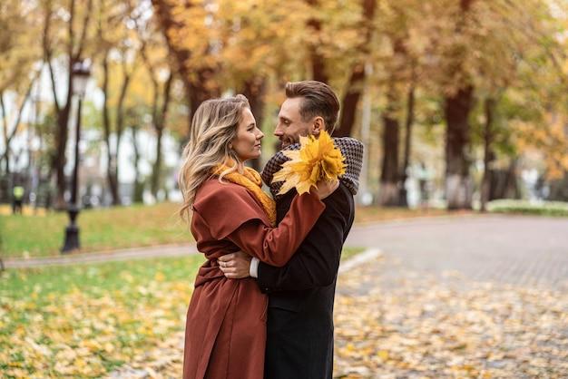 Насчет поцелуя. муж и жена обнялись улыбаются, глядя друг на друга в осеннем парке. открытый
