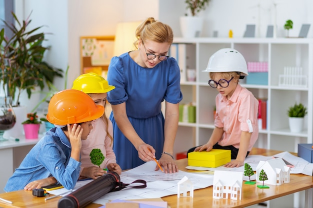 About house modeling. blonde-haired primary school teacher telling her pupils about house modeling