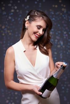 シャンパンのボトルを開こうとしています