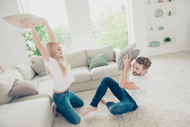 실내 베개와 싸우는 귀여운 커플의 높은 각도보기 위