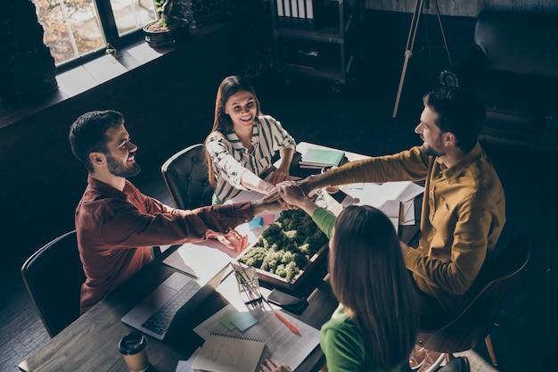 Вид сверху на четырех симпатичных жизнерадостных опытных деловых людей в повседневной формальной одежде и рукопожатие.