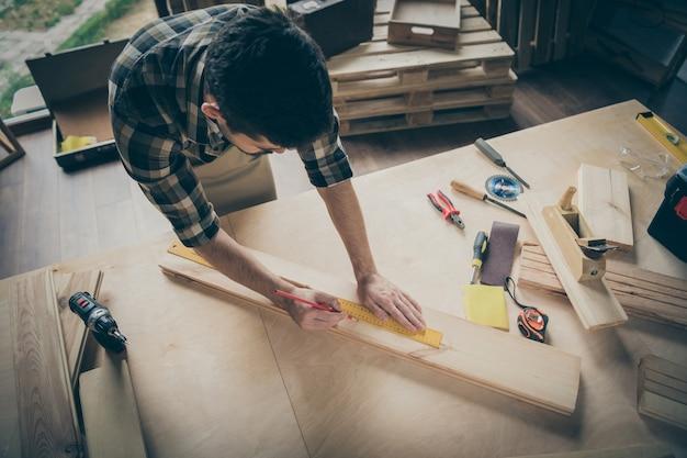 Над портретом под большим углом он симпатичный, привлекательный, сосредоточенный, опытный, трудолюбивый парень, создающий строительный проект дома, современный промышленный лофт, интерьер в стиле кирпича в помещении.