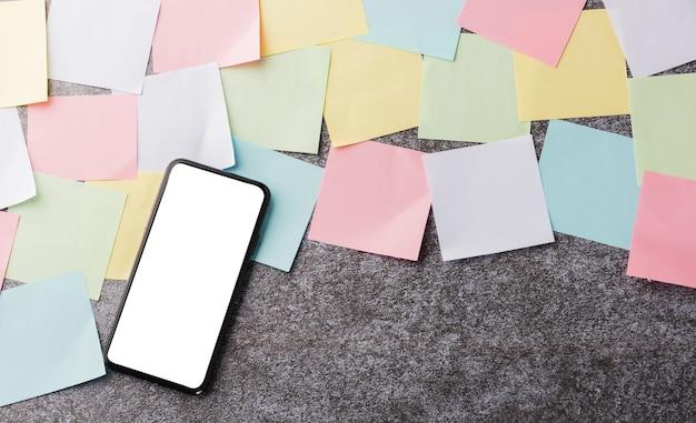 現代の黒いスマート携帯電話の空白の画面で多くの白紙の付箋リストの上に