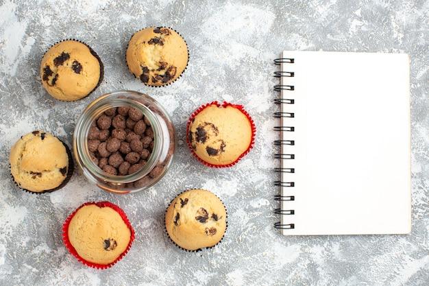 氷の表面のノートブックの横にあるガラスの鍋にチョコレートクッキーの周りのおいしい小さなカップケーキの上