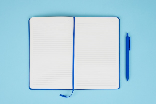 頭上のクローズアップパステルカラーの青い背景の上に分離された空のページとペンでメモ帳の写真画像を表示