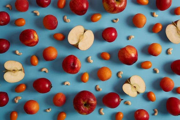 Выше выстрел из красных спелых яблок, персиков, томарилло, кумквата и питательных орехов кешью на синем фоне. креативная композиция из вкусных фруктов. сладкая еда с виаминами, концепция здорового питания