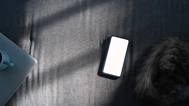 위 샷된 스마트 폰 빈 디스플레이 및 소파에 고양이.