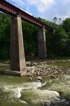 난간이 있는 보행자용 다리가 긴 콘크리트 기둥 위에 솟아 있습니다. 여름에 촬영, 사람이 없다