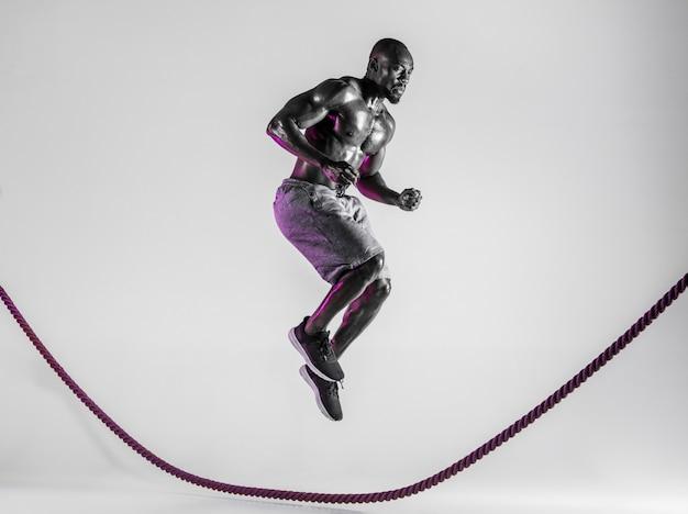 Над миром. молодой афро-американский культурист тренируется на сером фоне студии. мускулистая мужская модель в спортивной одежде прыгает через боевую веревку. понятие о спорте, бодибилдинге, здоровом образе жизни.