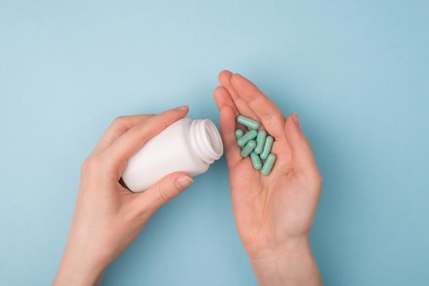 Выше сверху от первого лица крупным планом вид фото рук, измеряющих дозу, чтобы вылить таблетки из пластикового контейнера, изолированного на синем фоне