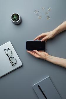 灰色の机で作業中に空白の画面でスマートフォンを保持している女性の手の背景を表示します。